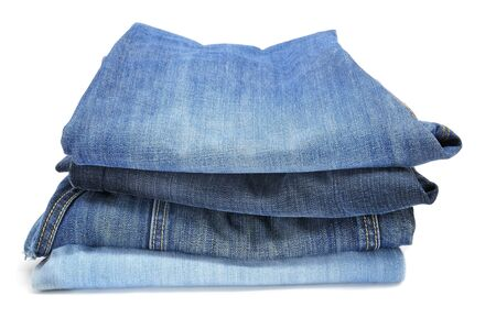 blue  jeans: a pile of folded blue jeans on a white background