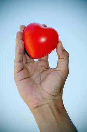 battement du coeur: une main tenant un coeur rouge sur le ciel.