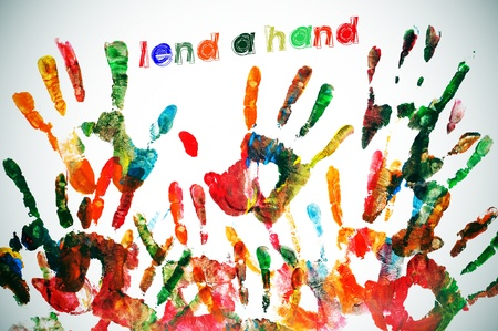 lend a hand written on a background full of handprints of different colors Stock Photo - 9421742