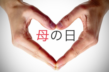hand written: hands forming a heart and the sentence happy mothers day written in chinese
