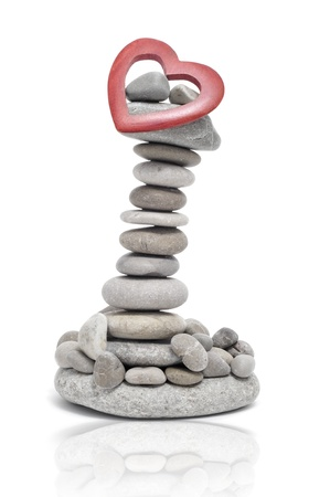 rock pile: a pile of zen stones and a wooden heart on a white background
