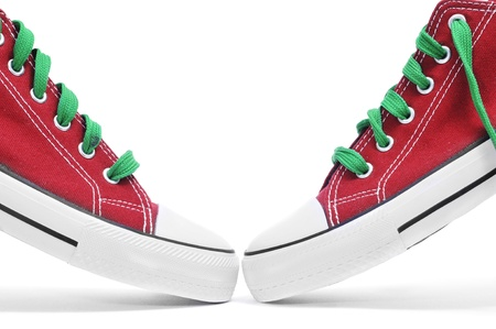 a pair of red sneakers with green shoelaces on a white background