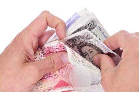 sterlina: qualcuno contando sterline su sfondo bianco