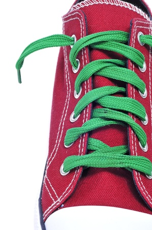 closeup of a red sneaker with green shoelaces on a white background photo