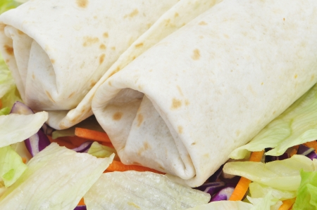 closeup of a pair of mexican burritos with salad photo