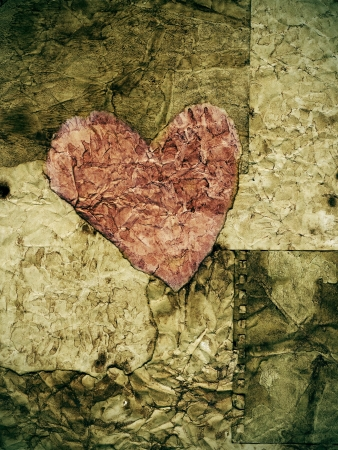 nostalgic: old paper heart in a background of textured old paper Stock Photo