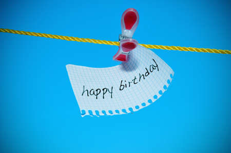 birthday wishes: happy birthday written in a notepaper hung on a clothesline