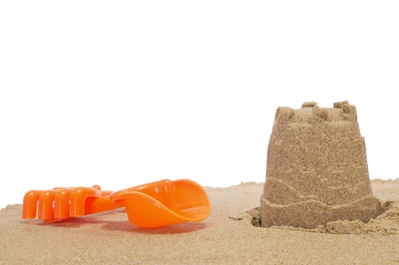 sand toys: a sandcastle with shovel and rake on a white background