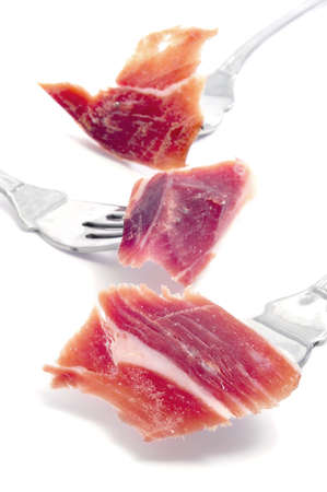 some slices of serrano ham in fork on a white background photo