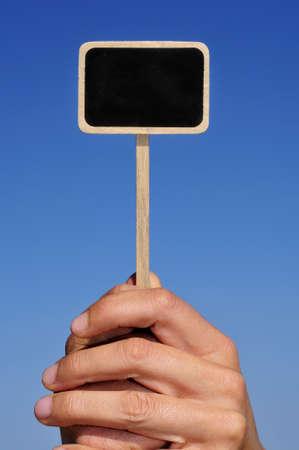 broaching: somene holding a blank blackboard label over the sky