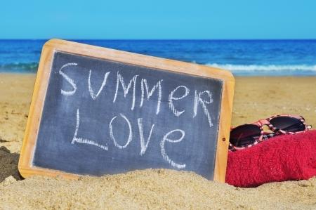 una lavagna con l'estate amore frase scritta su di esso, in asciugamano e gli occhiali da sole sulla spiaggia Archivio Fotografico