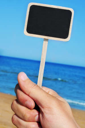someone holding a blank blackboard label at the beach Stock Photo - 9729196