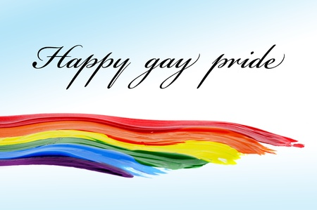 lgbt: Happy gay pride written in a background with a rainbow painted on it Stock Photo