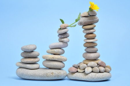 some piles of zen stones and yellow daisy on a blue background Stock Photo - 9889049