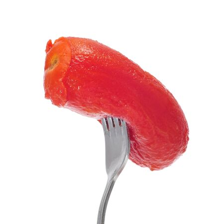 a roasted peeled tomato in a fork on a white background Stock Photo - 9889012