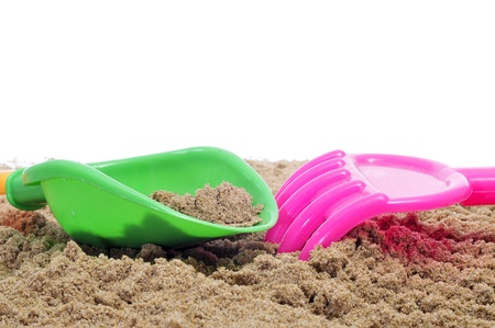 closeup of a beach shovel and a beach rake on the sand photo