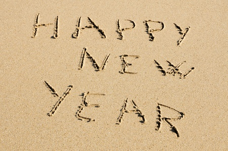 rest in peace: happy new year written in the sand of a beach