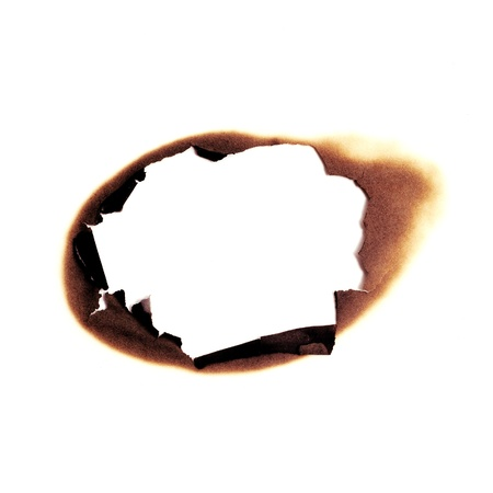 burned hole on a white paper background photo
