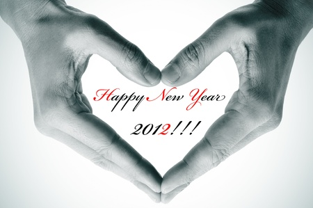 vignetted: happy new year 2012 written inside a heart made with the hands