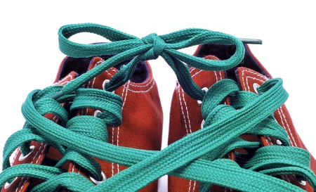 lace up: closeup of a pair of red sneakers with green shoelaces