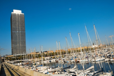 Barcelona, Spain - January 22, 2011: Torre Mapfre and Port Olimpic in Barcelona, Spain. This 44-story building is placed near the marina built for the 1992 Olympic Games
