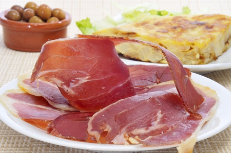 some spanish tapas, as tortilla de patatas, serrano ham and olives photo