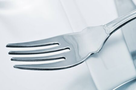 mealtime: closeup of fork and a knife on a white plate