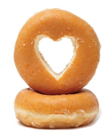 postres: donuts con un agujero en forma de coraz�n sobre un fondo blanco Foto de archivo