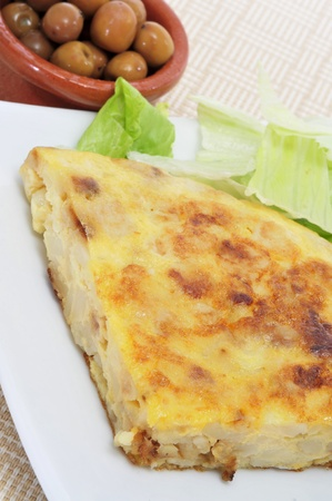 closeup of a typical spanish tortilla de patatas and a bowl with olives photo