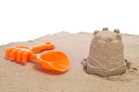 a beach shovel, a beach rake and a sandcastle on a white background photo