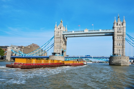 thames: A cargo ship in front of Tower Bridge in London, United Kingdom