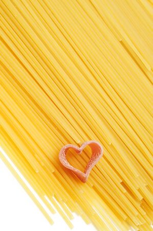 a pile of uncooked spaghetti with a heart-shaped pasta photo