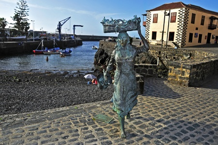 homage: Puerto de la Cruz, Spain - June 15, 2011: A sculpture of a fishwife in the fishing port in Puerto de la Cruz, Spain. This sculpture, from Julio Nieto, pays homage to the ancient fish vendors of town  Editorial