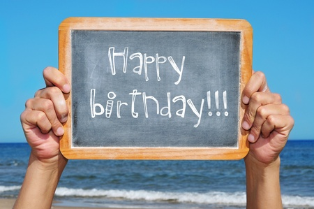 wishes: someone holding a blackboard with the sentence happy birthday written in it