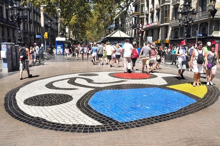 ramblas: Barcelona, Spain - August 16, 2011: Joan Miros Pla de lOs mosaic in La Rambla, Barcelona, Spain. Thousands of people walk dayly on the mosaic, designed by famous artist Joan Miro