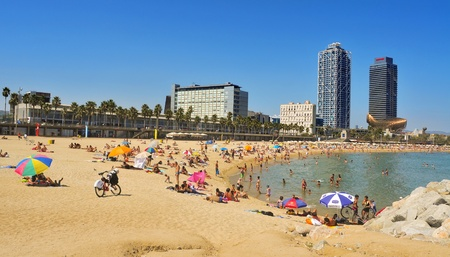 Barcelona, Spain - August 16, 2011: Barceloneta Beach with Hotel Arts in the background in Barcelona, Spain. Hotel Arts is a 44-story, 483 room luxury hotel on the seafront of the city
