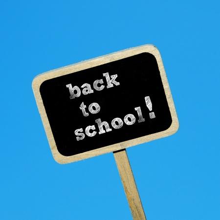 broaching: sentence back to school written in a blackboard label on a blu background