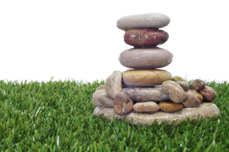 a pile of zen stones on the grass on a white background photo