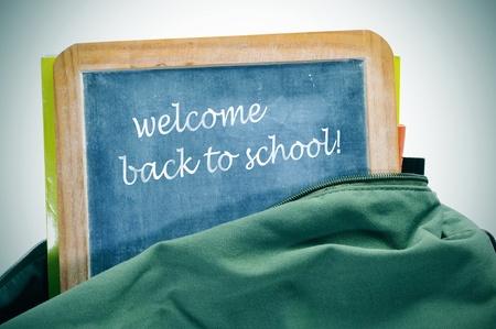 sentencia de la bienvenida de nuevo a la escuela por escrito en una pizarra en una mochila con los libros Foto de archivo - 10453727