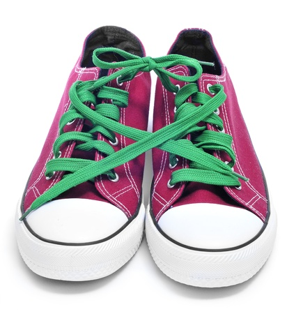 lace up: a pair of red sneakers with green shoelaces on a white background