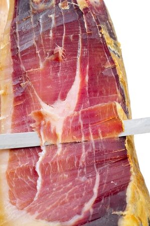 closeup of a knife cutting spanish serrano ham photo