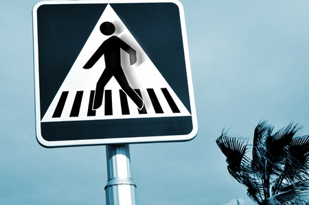 a pedestrian crossing sign with the silhouette of the person in motion photo