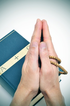 someone praying on a bible with a rosary Stock Photo - 10526925