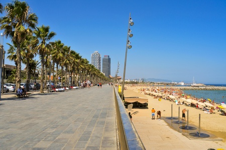 promenade: Barcelona, Spain - August 16, 2011: Barceloneta Beach with Hotel Arts and Mapfre Tower in the background in Barcelona, Spain. Arts is a 44-story hotel and its twin, an office building
