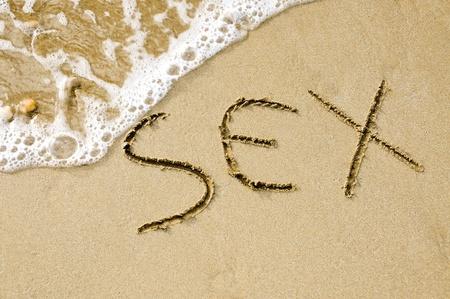sex: woord geslacht geschreven op het zand van het strand Stockfoto