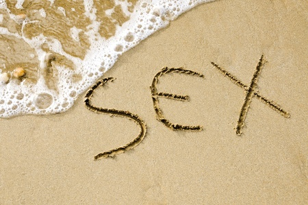 geschlechtsakt: Wort Geschlecht geschrieben auf dem Sand des Strandes