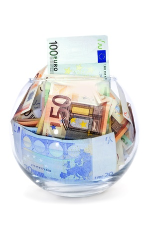 thrift box: a pile of euro bills into a glass money box