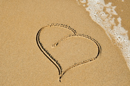 evoking: a heart carved on the sand of a beach Stock Photo
