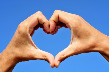 man hands forming a heart over the blue sky Stock Photo - 10704480