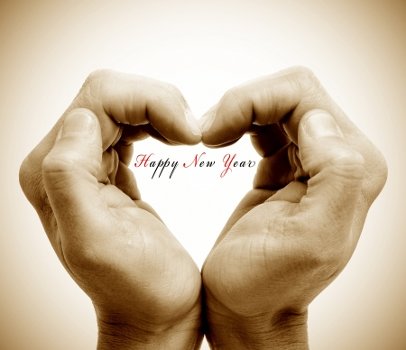 vignetted: hands forming a heart and the sentence happy new year Stock Photo